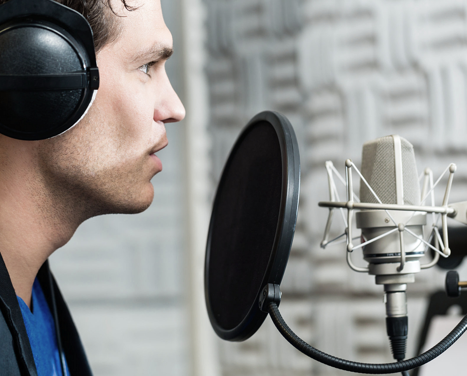 Male singer recording in a studio